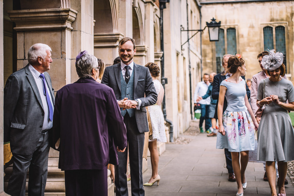 groom meeting guests at pembroke college wedding photography
